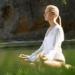 A woman meditates in an open field of flowers.