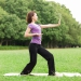 Woman doing tai chi on grass