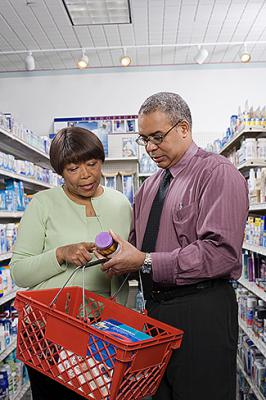A man and woman look at the label of a pill bottle.