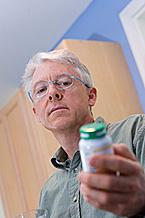 Older man reading the label on a pill bottle.