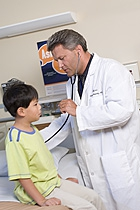 Doctor using sthethoscope to check patient.