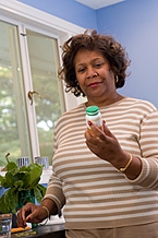 Woman examining a pill bottle.