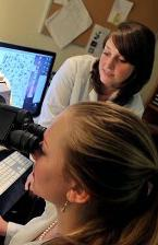 A research mentor (Lori Eidson) and student (Nina Waldron, on the microscope).