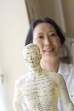 A doctor holds out a human model on which acupuncture points are marked.