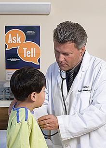 A doctor looks at a child patient.