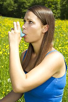A woman user an inhaler in a field of flowers.