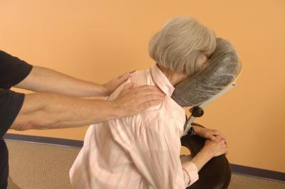 A woman receives seated massage.