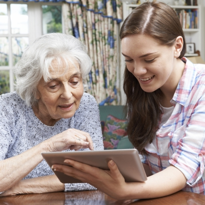 Young woman helping an older woman use a tablet
