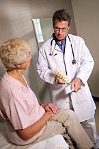 Doctor showing bone model to elderly woman