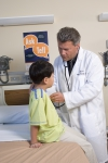A doctor examines a boy. A Time to Talk poster is in the background.
