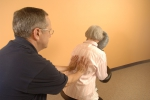 Massage therapist providing seated massage.