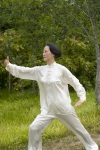 A woman practices Tai Chi outside.