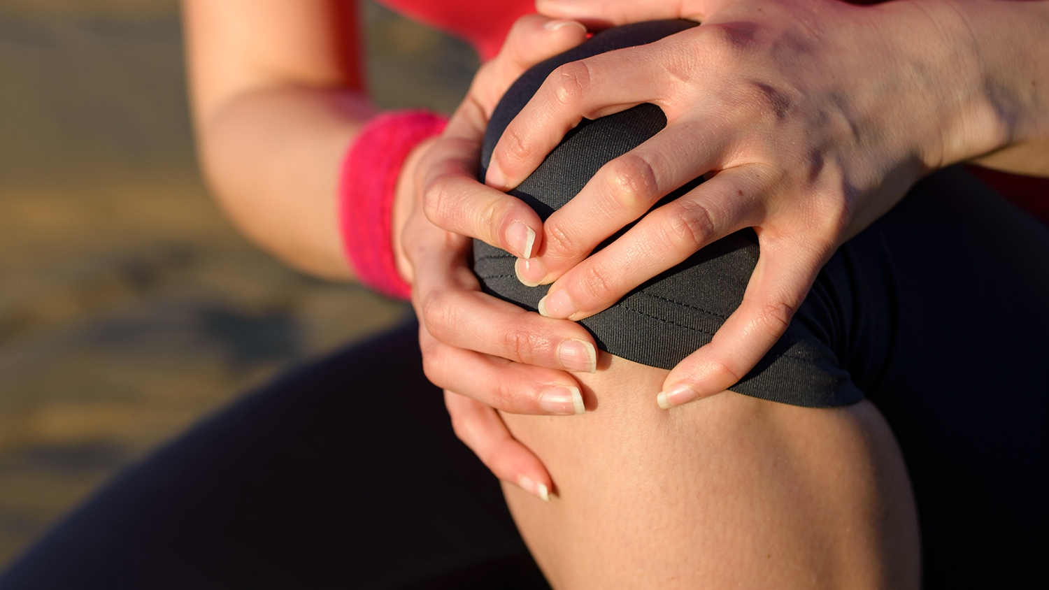 Woman holding her knee in pain from arthritis