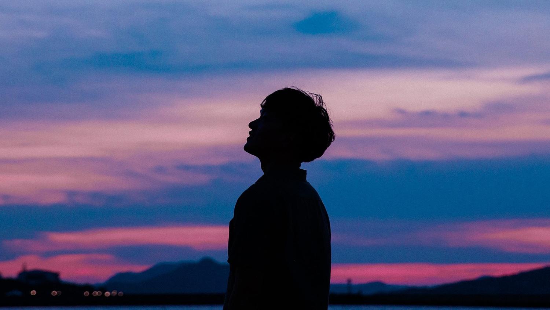 man looking into sky over ocean