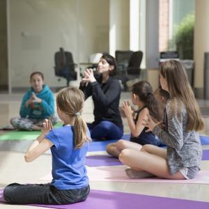 Yoga instructor teaching kids a pose