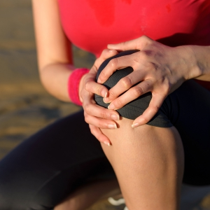 Woman holds her knee in pain from arthritis.