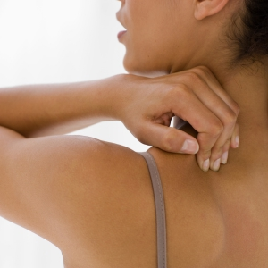 Woman massages pain on her upper back