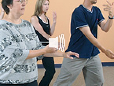 Two women and a man doing Tia Chi.