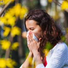 Woman outside blowing her nose in a tissue