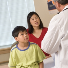 A mother and son talk to a doctor.