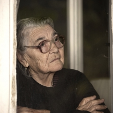 An older woman looks out the window.