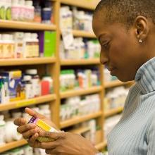 Woman examining a pill bottle.