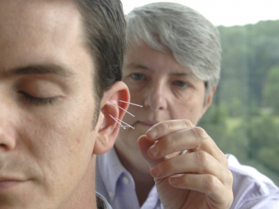 Acupuncturist inserts needles into a man's ear.