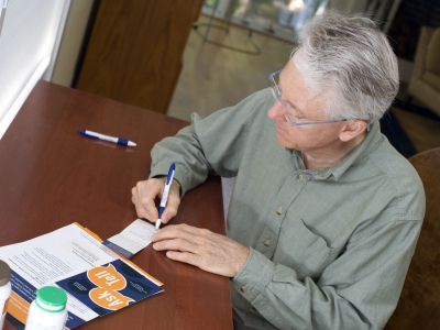 A man fills out a Time to Talk patient wallet card.