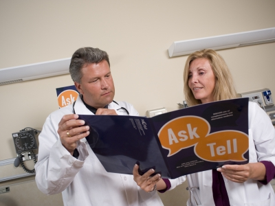 Two doctors review a folder of Time to Talk campaign material.