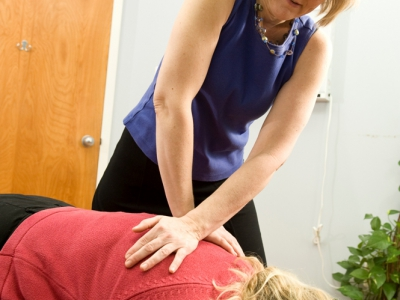 A chiropractic doctor provides an adjustment to a woman on a table.