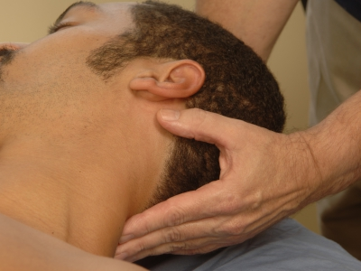 Massage therapist manipulating the head and neck during a massage session.