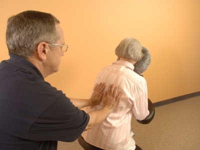 Massage therapist providing seated massage.