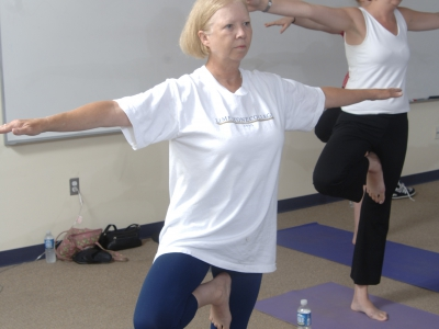 Woman practicing yoga tree pose.