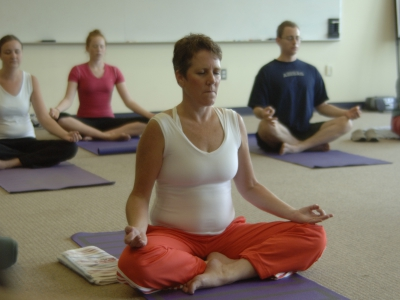 Participants in a yoga class meditating while in the lotus pose.