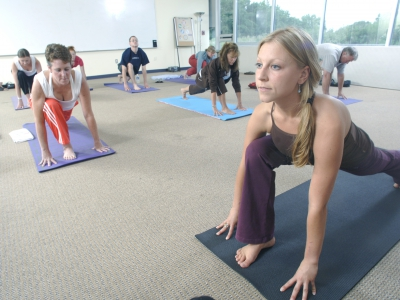 Yoga instructor demonstrates a lunge pose.