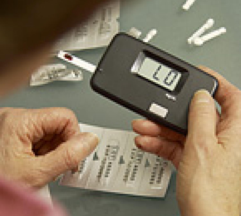 A mature adult Caucasian female checking her blood sugar.