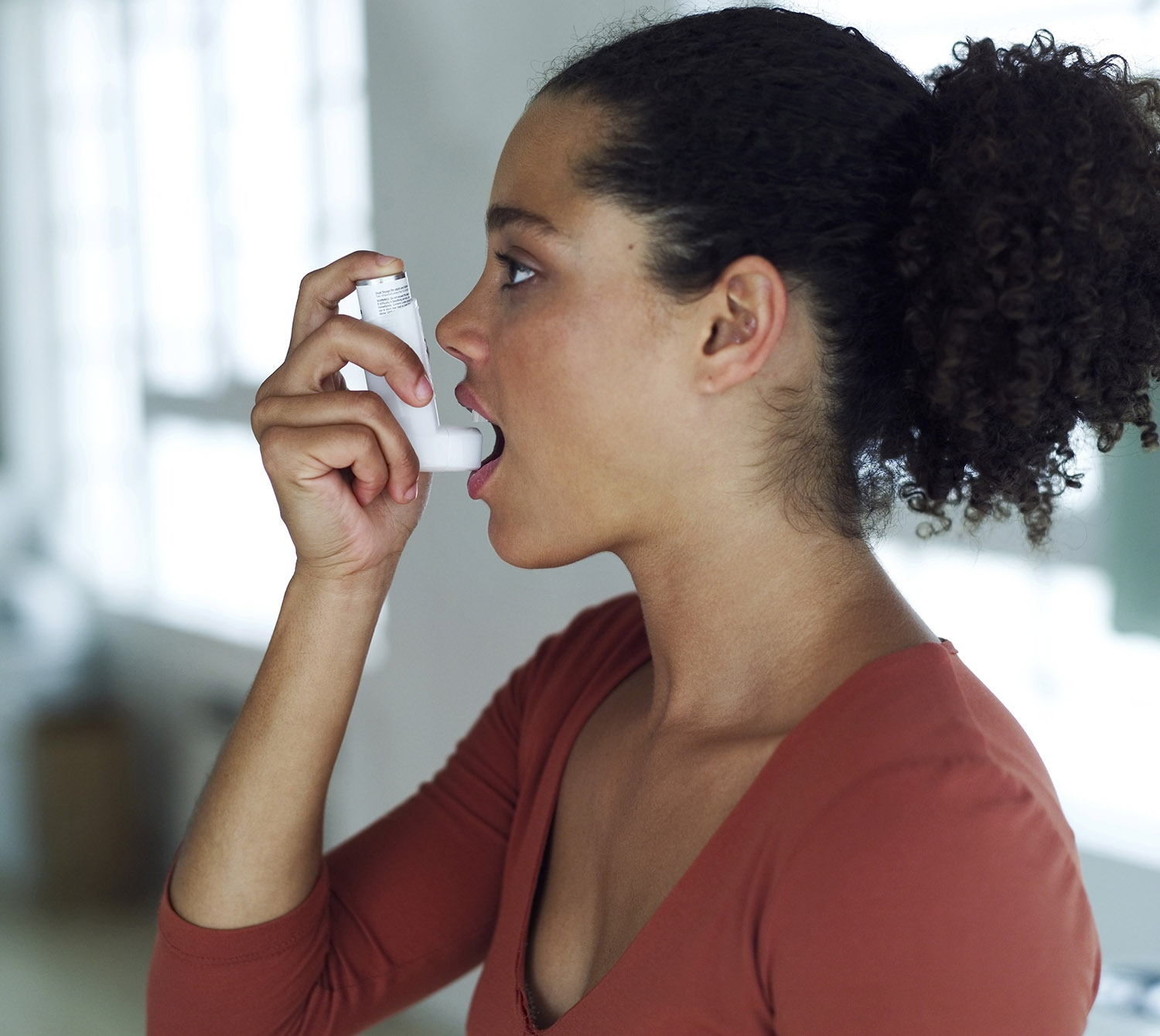 A young woman about to use an inhaler.