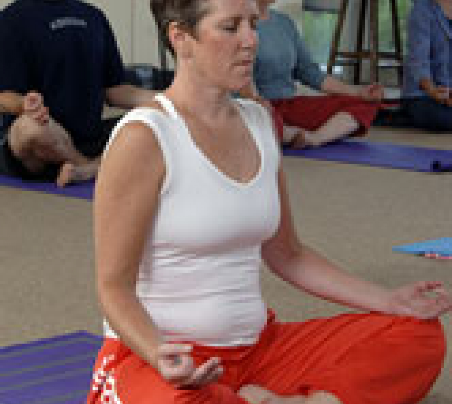 A woman Meditating during a yoga class.