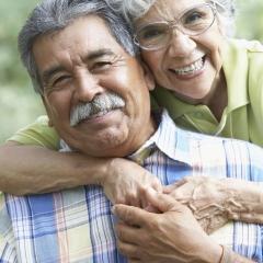 Older Hispanic couple holding each other