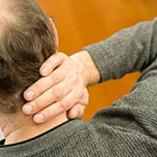 A man touching his neck.