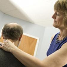 A chiropractor examines a patient.