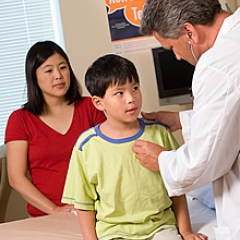 A doctor looks at a child patient while the mother observes.