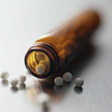 Open pill bottle, pills spilling out.