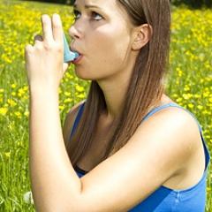 A woman user an inhaler in a field of flowers.