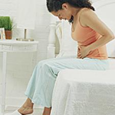 Woman sitting on bed holding stomach, head bowed.