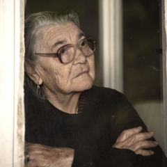 An older woman looks out the window. © iStock/fotostorm