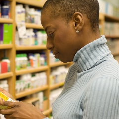 Woman examining a pill bottle. © JupiterImages