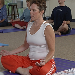 A woman practices a meditative yoga pose.