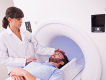 A doctor speaks to a patient who is in place to be entered into a CAT scan machine.