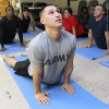 A man in an army shirt practices yoga.